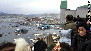 Japanese residents survey the damage after the March 11 tsunami, which was detected by radar.