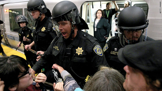 BART police hold back demonstrators who are trying to prevent a train from leaving its station on Monday.