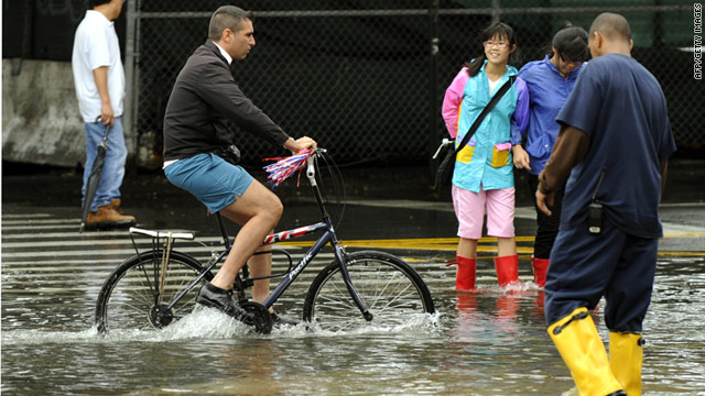 A man rides a bike through floodwaters on South Street in New York on Sunday.