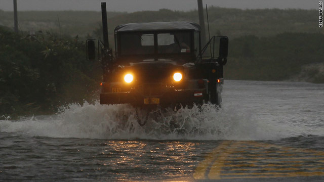 An Army vehicle drives down a flooded road in Southampton, New York, on Sunday.