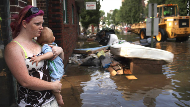 A woman and her baby look out over a flooded street Wednesday in Wallington, New Jersey.