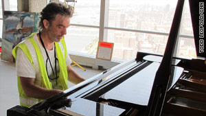 Artist Marcus Robinson, taking a break at a piano in his 48th-floor studio, is chronicling the area's construction.