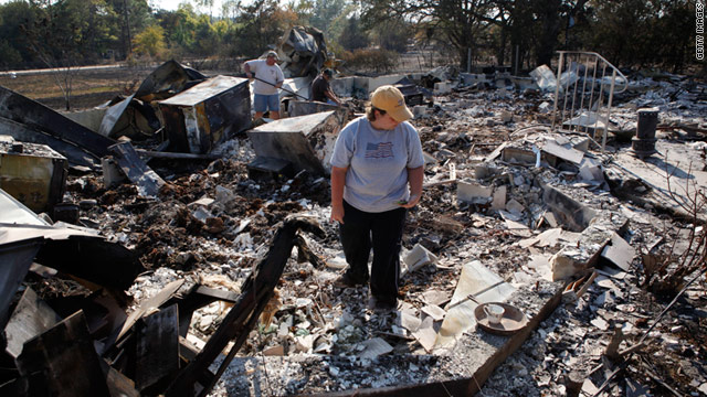 Hillary Polly looks through the rubble of her family's burned house on Wednesday near Bastrop, Texas.