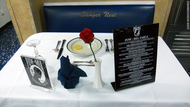 A small table covered in a simple cloth on board the USS Wasp pays tribute to the 83,000 prisoners of war and missing in action.