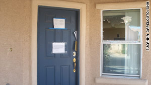 A notice on the door of a North Las Vegas home says it's vacant. The windows have been broken out.