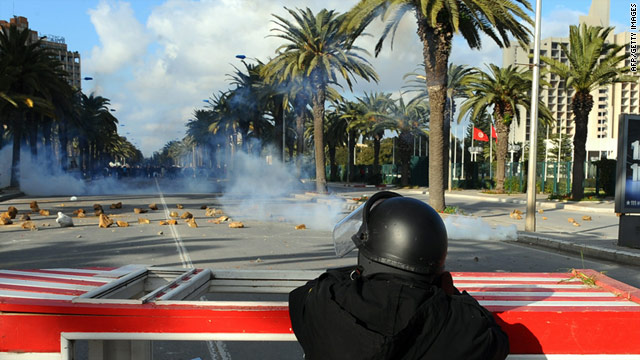A security officer fires tear gas toward demonstrators Friday on a street in Tunis, Tunisia.