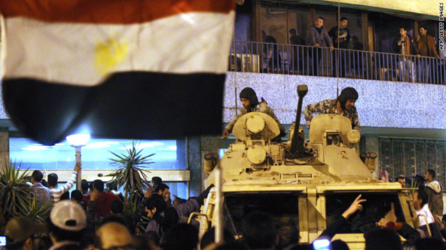 Egyptian protesters gather around the national television building as members of the presidential guard stand by Friday in Cairo.