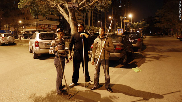 Egyptian civilians carrying batons and sticks stand guard in a Cairo street to protect their properties from looters.