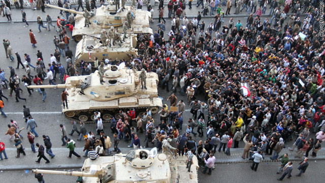 Egyptian demonstrators demanding the resignation of President Mubarak carry the body of a dead protestor past army tanks.