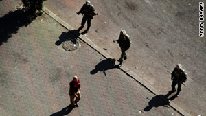 A man walks past soldiers on Monday in Cairo. Egypt's military has indicated it sympathizes with protesters.
