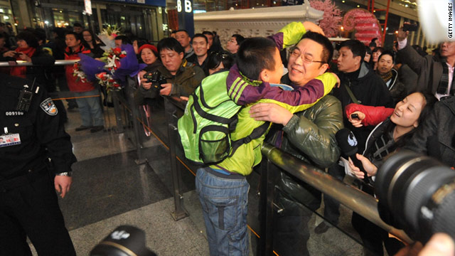 A young passenger returning from Egypt hugs a member of his family at Beijing airport on Tuesday.