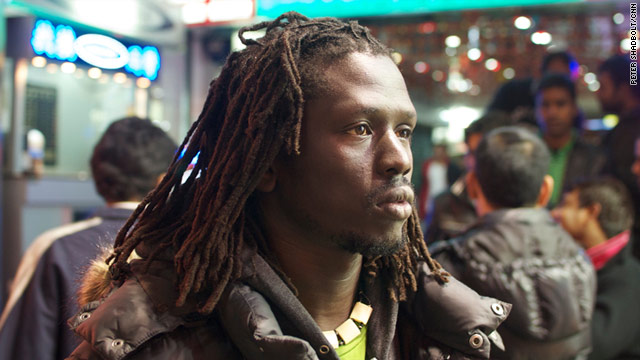 Sudanese rapper and former child soldier Emmanuel Jal stands outside Hong Kong's Chungking Mansions.