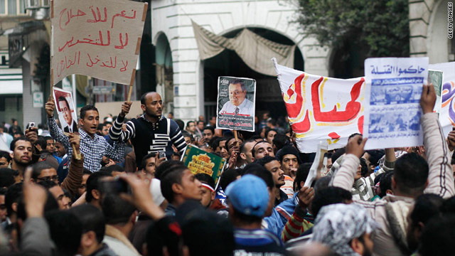Government backers, left, holds signs in front of anti-government protesters, foreground, at Cairo's Talaat Harb Square.