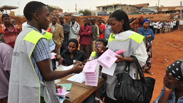 Polling workers get ready to open a voting station as people wait in line at a polling station in Uganda's capital Kampala.