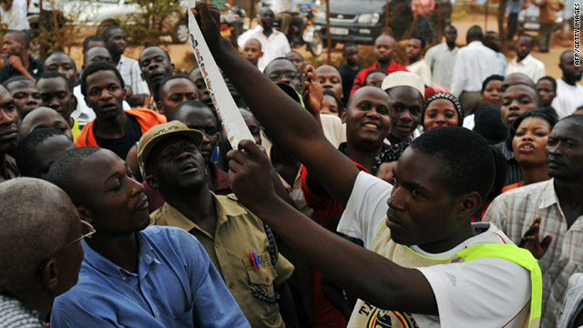 A poll worker shows a vote to people wanting to see after the vote counting started in Kampala, on February 18, 2011