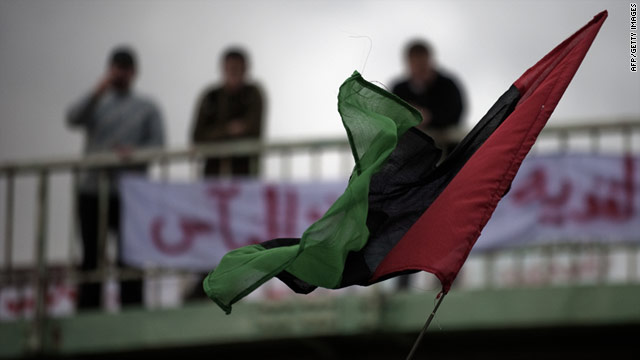 Libya's old national flag flutters in front of a bridge during an anti-Gadhafi protest in the eastern Libyan town of Derna.