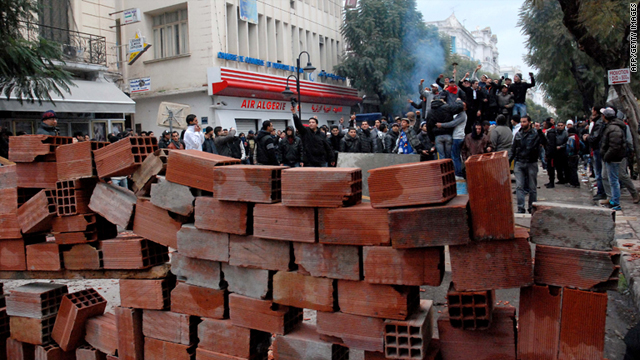 Tunisian demonstrators stand behind a barricade as they clash with Tunisian security forces during an anti-government protest in Tunis on February 26, 2011.