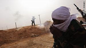 A tribal rebel fires a rocket-propelled grenade from a militia post on February 27 in Ajdabiya, Libya.