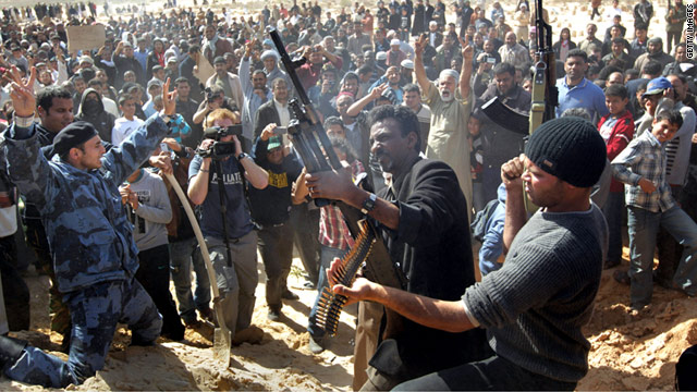 Rebel fighters shoot into the air during a funeral for slain comrades in Ajdabiya, Libya.