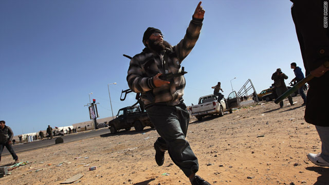 A rebel runs for cover during a government airstrike in the area of Ras Lanuf, Libya, on Monday.
