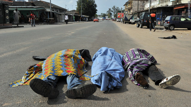 The bodies of three people killed in a street of the popular Abidjan district of Adjame as civil unrest rages on Friday.