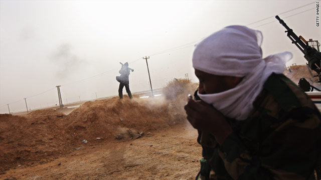 A tribal rebel fires a rocket-propelled grenade from a militia post on February 27 in Ajdabiya, Libya.