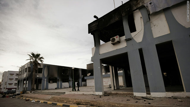 Libyan youths walk past a burnt out building in this file picture in the eastern Libyan town of Derna on February 23, 2011.
