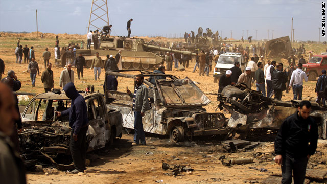 Libyans gather March 21 at a site near Benghazi where Gadhafi's forces were targeted by a French air strike.