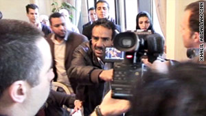 CNN photojournalist Khalil Abdallah, far left, holds his camera tight while a man tries to snatch it.