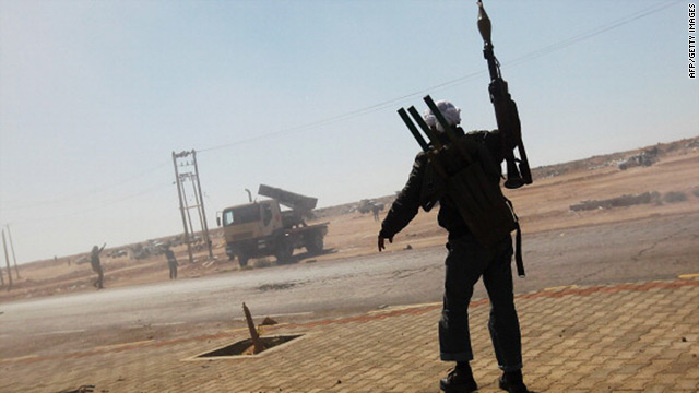 Rebel fighters celebrate after firing powerful rockets toward Libyan Army positions near Ajdabiyah April 11, 2011. 