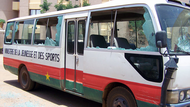 A bus sits on a street in Burkina Faso with its windows smashed due to the unrest.