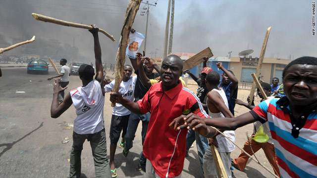 Demonstrators wave sticks in Kano, Nigeria, on Monday as preliminary results of Sunday's voting are released.