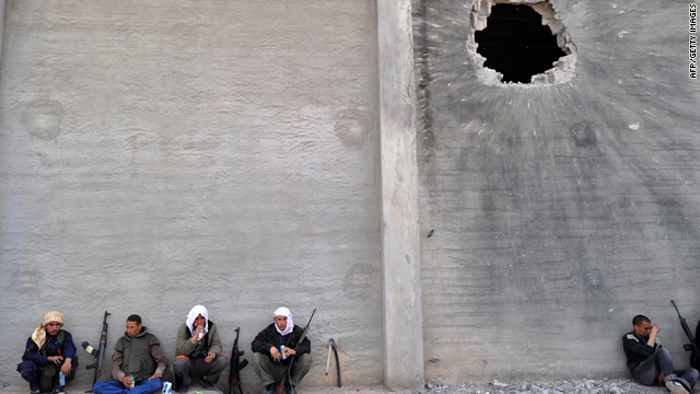 Libyan rebels rest close to a building where pro-Gadhafi forces are reportedly holed up in Misrata on Sunday.