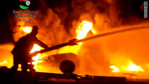 Libyan rebel fighters attempt to put out a fire Saturday at a fuel depot in Misrata.