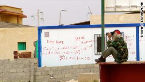 Near the Libya-Tunisia border, a rebel spotter watches rockets strike a few kilometers from the vital crossing.