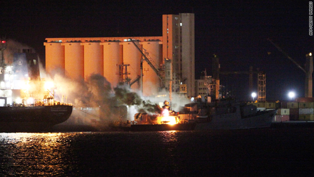 Smoke rises from a fire on a boat on Thursday in Tripoli after NATO air strikes targeted the port of the Libyan capital.