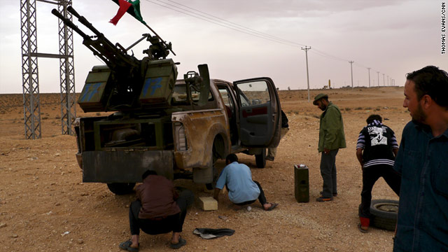 Libyan rebels change a tire on a gun truck on the road from the Tunisian border to the rebel-held town of Zintan.