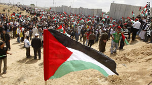 Palestinians hold up their flag as they rally along the Rafah border.