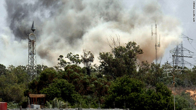 Smoke billows behind the trees following an air raid on Tajura, about 30 kilometers (18.6 miles) east of Tripoli on Tuesday.
