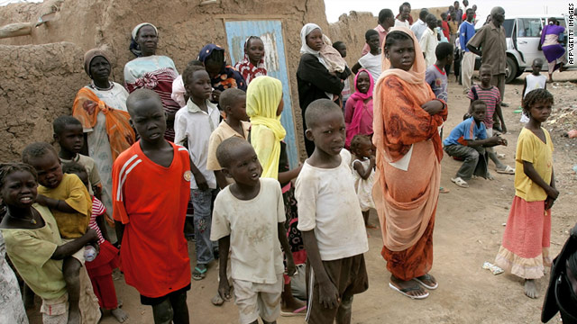 Children and women look on at the Mandela camp for displaced southern Sudanese, 30 kilometers south of Khartoum, on May 22.  (Photo Courtesy of CNN)
