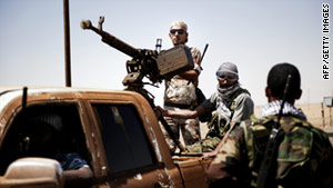 Libyan rebels arrive in the area of Ajdabiya, Libya, on Thursday, having returned from al-Brega.