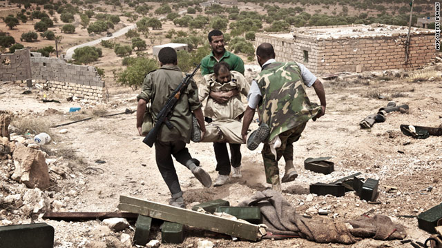 Libyan rebels carry away a comrade wounded during fighting with forces loyal to Libyan leader Moammar Gadhafi on June 7.