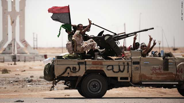 Libyan rebel fighters flash the victory sign as they drive on June 11, 2011 in Ajdabiya, south west of Benghazi.