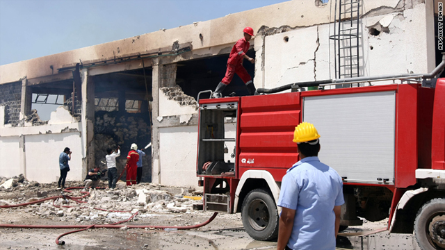 Libyan fire fighters survey the remains of a food storage building damaged during a NATO airstrike in Zlitan, Libya, on July 25.