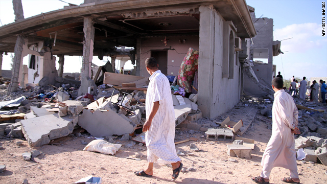 People walk past destroyed buildings on Monday, in Majer, south of Zliten.