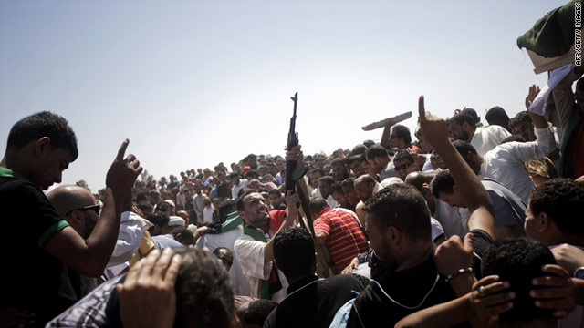A Libyan mourner fires shots in the air at a cemetery on August 12 during the funeral of five rebels killed in battle.