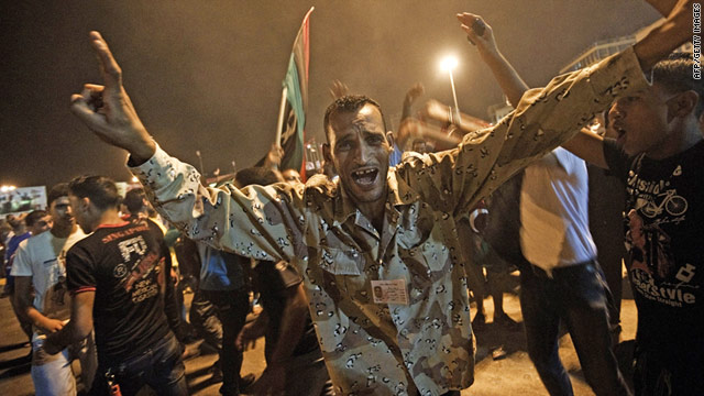 A Libyan rebel fighter in Benghazi celebrates the news one of Moammar Gadhafi's sons has been captured in Tripoli.