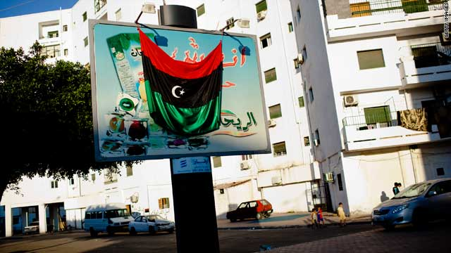 A Libyan rebel flag is hung across a billboard on August 25, 2011 in Tripoli.