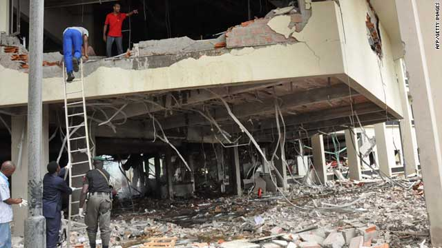 Police and rescue workers stand in the debris of the premises of the United Nations' building in Abuja on Friday.