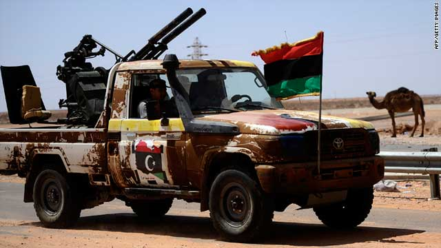 Rebel fighters sit in a vehicle on the road between Misrata and Sirte, Moammar Gadhafi's hometown, on Tuesday.